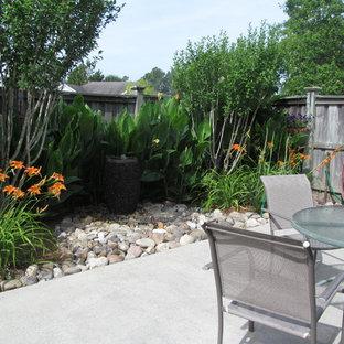 Foto di un patio o portico tropicale di medie dimensioni e dietro casa con fontane, ghiaia e un parasole