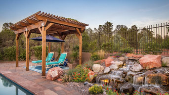 Waterfall by Pond. Pergola Covered Seating Area