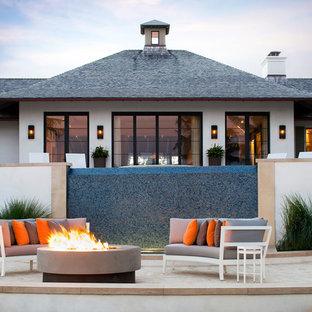 Ispirazione per un patio o portico tropicale con un focolare