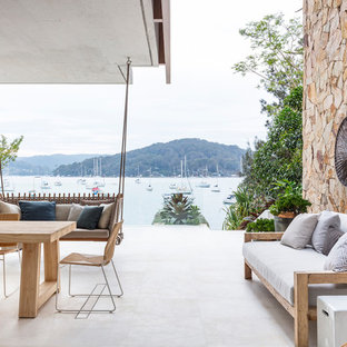 Inspiration for a beach style patio in Sydney with a container garden, concrete slab and a roof extension.