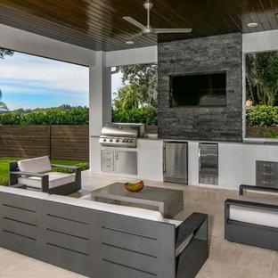 Ispirazione per un patio o portico moderno dietro casa con pavimentazioni in pietra naturale e un tetto a sbalzo