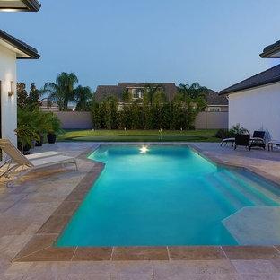 Ispirazione per un patio o portico minimalista di medie dimensioni e dietro casa con piastrelle e un tetto a sbalzo