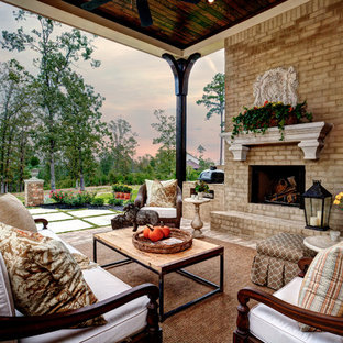 Example of a large classic backyard brick patio design in Little Rock with a roof extension and a fireplace