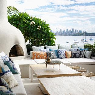 Ispirazione per un patio o portico stile marino dietro casa con nessuna copertura e un caminetto