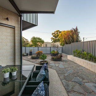 Inspiration for a medium sized eclectic back patio in Adelaide with a potted garden, concrete slabs and an awning.