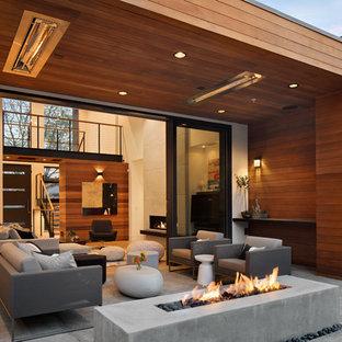 Inspiration för moderna uteplatser, med en öppen spis, betongplatta och takförlängning