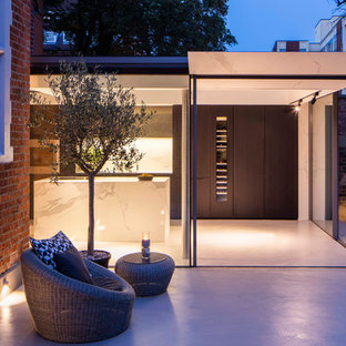 Design ideas for a medium sized modern back patio in London with concrete slabs and no cover.