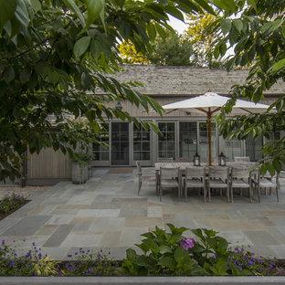 Esempio di un patio o portico country di medie dimensioni e dietro casa con pavimentazioni in pietra naturale e nessuna copertura