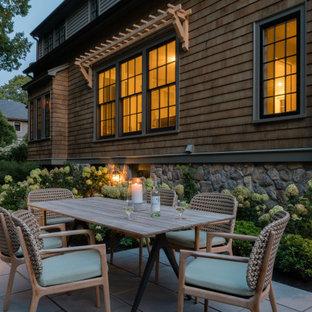 Réalisation d'une terrasse latérale tradition avec des solutions pour vis-à-vis et des pavés en pierre naturelle.