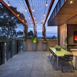 Foto på en funkis uteplats, med en vertikal trädgård, betongplatta och en pergola