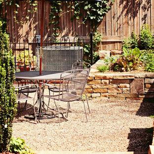 Modelo de patio tradicional, pequeño, en patio trasero, con huerto y gravilla