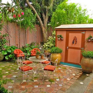 Immagine di un patio o portico boho chic di medie dimensioni e in cortile con un giardino in vaso, piastrelle e nessuna copertura