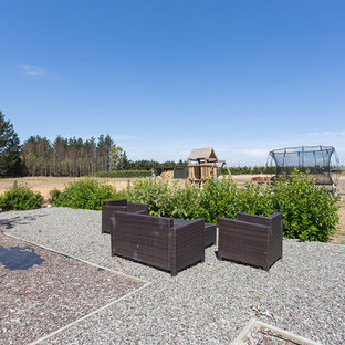 Foto på en stor lantlig gårdsplan, med utekrukor och granitkomposit