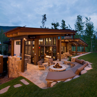 Example of a large mountain style backyard stone patio design in Denver with a fire pit and a roof extension