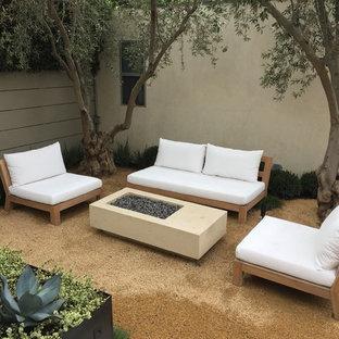 Ejemplo de patio moderno, de tamaño medio, sin cubierta, en patio trasero, con brasero y granito descompuesto