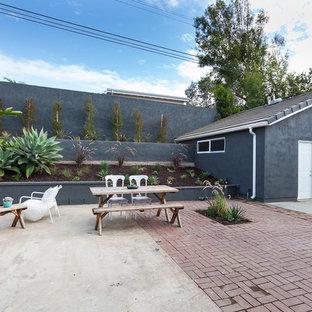 Midcentury modern brick patio photo in Other