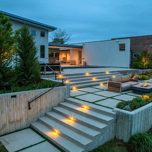 Example of a large minimalist backyard concrete paver patio design in Denver with a fire pit and no cover