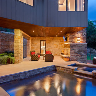 Patio - contemporary backyard patio idea in Austin with a fire pit and a roof extension