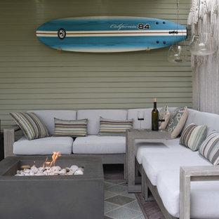 Photo of a small beach style back patio in Santa Barbara with a fire feature, concrete paving and an awning.