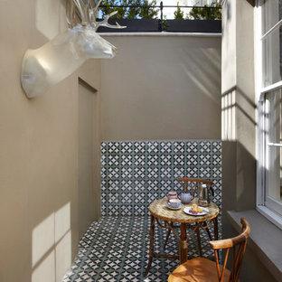 Imagen de patio ecléctico, pequeño, sin cubierta, con suelo de baldosas