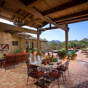 Cette image montre une terrasse méditerranéenne avec un foyer extérieur et une extension de toiture.
