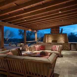 Idée de décoration pour une grande terrasse avec une cuisine extérieure arrière sud-ouest américain avec des pavés en pierre naturelle et une extension de toiture.