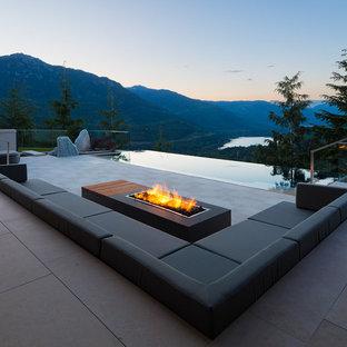 Foto di un grande patio o portico minimalista dietro casa con un focolare, lastre di cemento e nessuna copertura