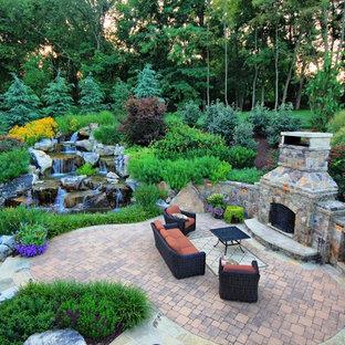 Modelo de patio clásico, grande, en patio trasero, con adoquines de ladrillo y chimenea