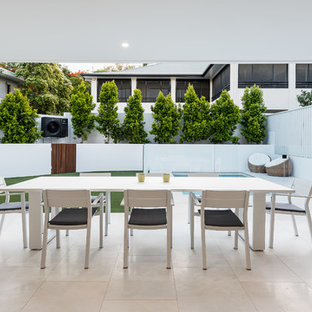 Inspiration for a small modern backyard patio in Brisbane with tile and a roof extension.