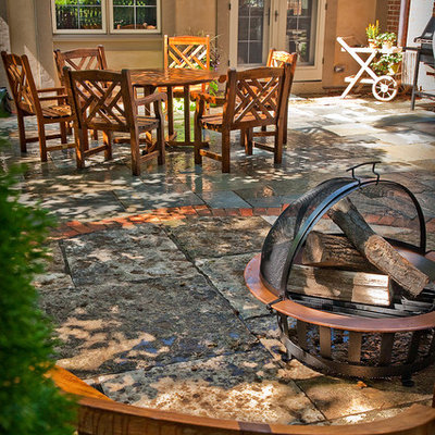 Example of a mid-sized classic backyard stone patio design in Milwaukee with a fire pit