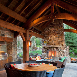 Exemple d'une terrasse montagne avec un foyer extérieur et une extension de toiture.