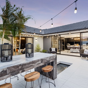 Contemporary backyard patio in Perth with a water feature, natural stone pavers and no cover.