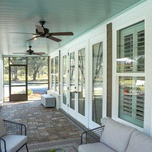 Ispirazione per un patio o portico tradizionale di medie dimensioni e dietro casa con pavimentazioni in mattoni e un tetto a sbalzo