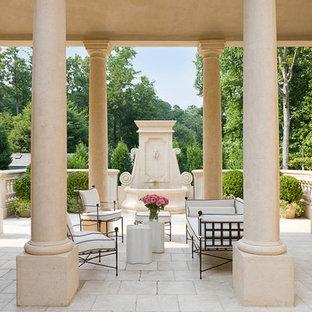 Foto di un grande patio o portico classico in cortile con fontane, un tetto a sbalzo e pavimentazioni in pietra naturale