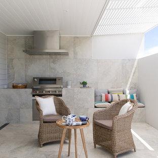Foto di un piccolo patio o portico moderno in cortile con piastrelle e un tetto a sbalzo