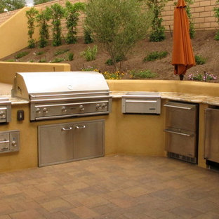 Photo of a medium sized mediterranean back patio in San Diego with an outdoor kitchen, concrete paving and no cover.
