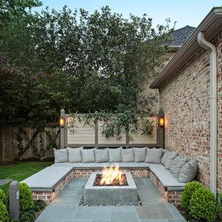 Immagine di un patio o portico chic di medie dimensioni e dietro casa con un focolare e pavimentazioni in pietra naturale