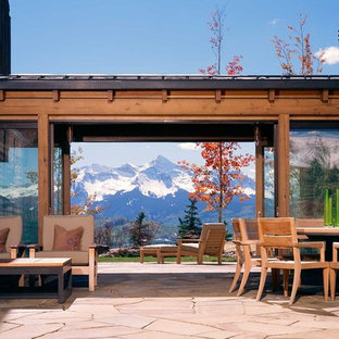 This is an example of a large country backyard patio in Denver with natural stone pavers and no cover.