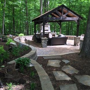 Ispirazione per un patio o portico american style di medie dimensioni e dietro casa con un focolare, pavimentazioni in mattoni e un gazebo o capanno