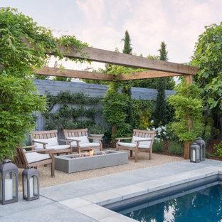 Ispirazione per un patio o portico di medie dimensioni con un focolare, una pergola e ghiaia