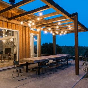 Esempio di un patio o portico country dietro casa con una pergola