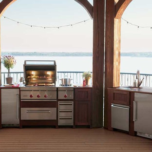 Patio kitchen - large traditional backyard patio kitchen idea in Other with decking and a pergola