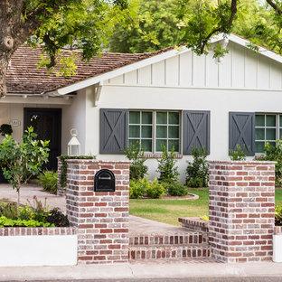 Immagine di un grande patio o portico stile americano davanti casa con pavimentazioni in mattoni e nessuna copertura