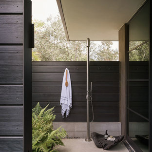 Photo of a midcentury patio in Orange County with an outdoor shower, concrete slab and no cover.