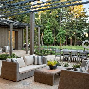 Ejemplo de patio de estilo de casa de campo, en patio trasero, con pérgola