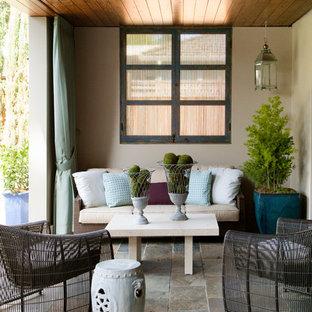 Idéer för en mellanstor modern uteplats på baksidan av huset, med takförlängning och naturstensplattor