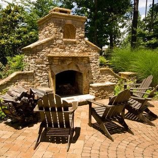 Immagine di un patio o portico chic con pavimentazioni in mattoni e un focolare
