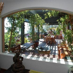 Ispirazione per un grande patio o portico etnico dietro casa con piastrelle e una pergola