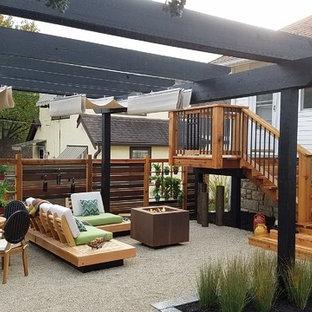Foto di un piccolo patio o portico moderno dietro casa con graniglia di granito e una pergola