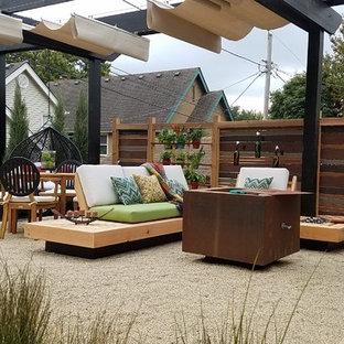 Esempio di un piccolo patio o portico moderno dietro casa con un focolare, graniglia di granito e una pergola